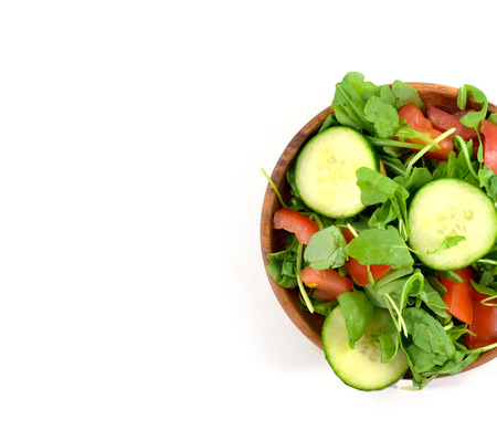 Organic arugula salad with tomato and cucumber slices on wood plate - isolated Imagens