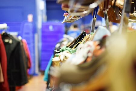 Rows of stylish womens shoes and high heels on a rack for sale at a clothing store