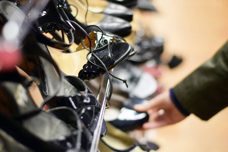 Hand shopping for shoes on a rack in clothing store Stock Photo