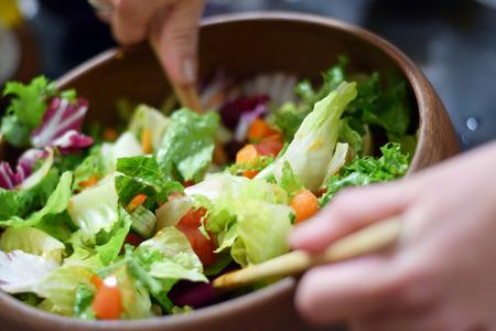 ensalada cesar: Manos de la mujer lanzando ensalada fresca en un plato de madera con estilo