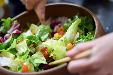 Womans hands tossing fresh garden salad in a stylish wooden bowl