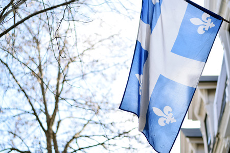 Quebec flag in Montreal billowing in the breeze outside Stock Photo