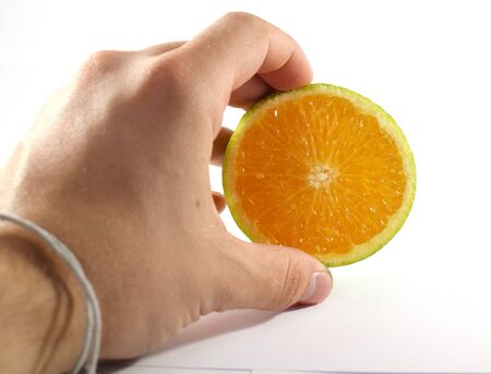 reticulata: Mans hand holding half of a cut orange fruit - isolated