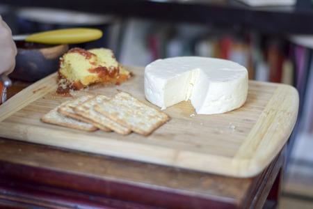 Traditional Brazilian cheese board (cheese from Minas Gerais) breakfast with wheat crackers, and bolo de fuba (Portuguese translation: cornmeal cake) with guava spread