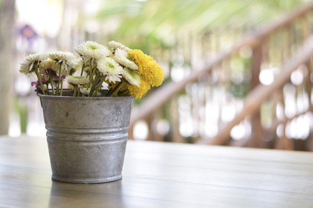 Rustic vintage metal flower pot on a wooden table with daisies Reklamní fotografie