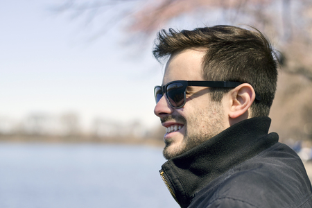 Handsome man on a walk looking out at water smiling away from camera Stock Photo