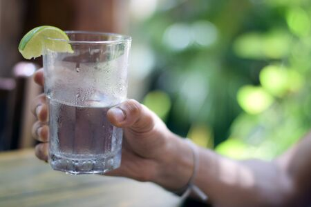 seltzer: Male hand holding water glass with condensation with lime wedge outside Stock Photo
