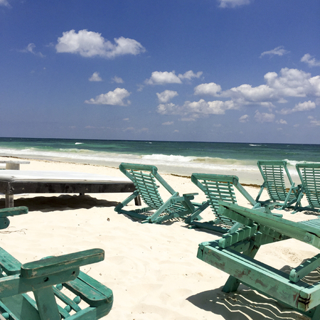 Wooden chairs on tropical beach in front of the ocean Stock Photo
