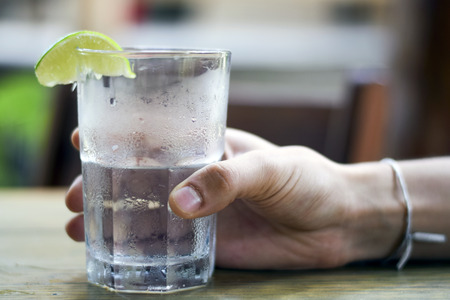 Male hand holding water glass with condensation with lime wedge outside Imagens