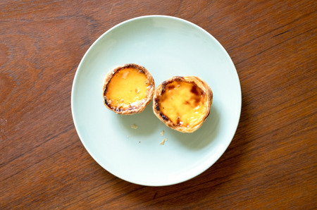 Authentic pastel de nata on a plate on a table.  Portuguese treat for breakfrast.