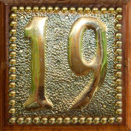 nineteen: Ottone e la targa di legno con il numero diciannove impresso su di esso