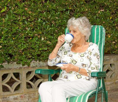 Senior lady enjoying a cup of tea in the garden photo