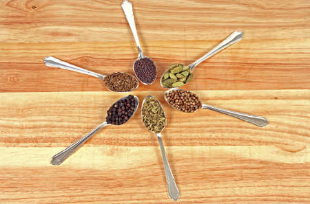 Six different whole spice seeds in silver spoons on a wooden background Stock Photo - 7673027