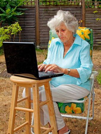 An elderly woman using a laptop computer in her garden photo