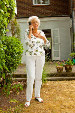 Senior lady in her garden recieves a phone call photo