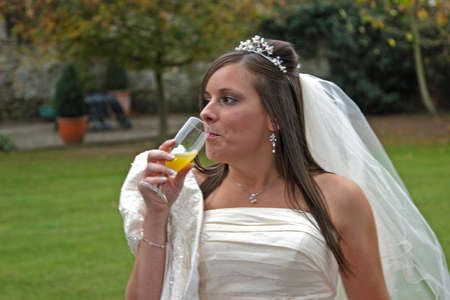 sipping: A young bride sipping a glass of Bucks Fizz