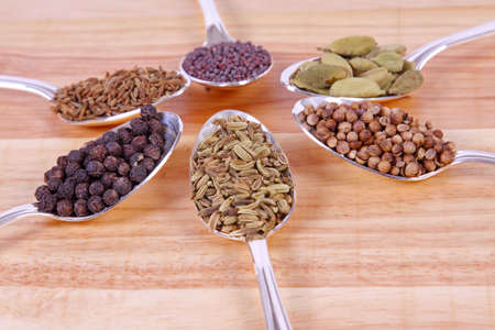 Six different whole spice seeds in silver spoons on a wooden background Stock Photo - 7786410