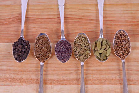 Six different whole spice seeds in silver spoons on a wooden background photo
