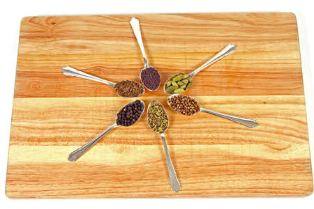 Six different whole spice seeds in silver spoons on a wooden chopping board against a white background. photo