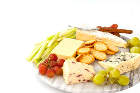 cheeseboard: A variety of cheeses with biscuits and garnishes on a marble cheeseboard isolated on white with copyspace