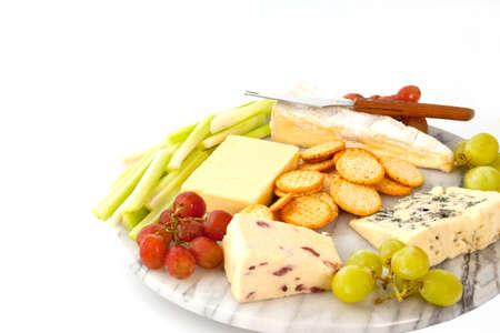 tabla de quesos: Una variedad de quesos con galletas y guarniciones en un cheeseboard de m�rmol aislados en blanco con copyspace