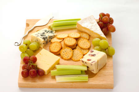 cheeseboard: A variety of cheeses with biscuits and garnishes on a wooden cheeseboard