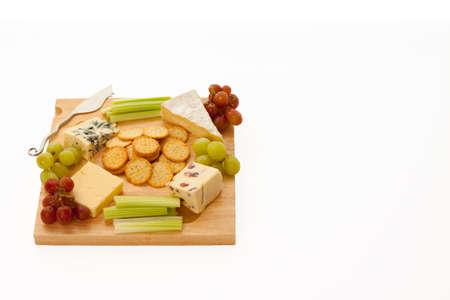 tabla de quesos: Una variedad de quesos con galletas y guarniciones en un cheeseboard de madera aislados en blanco con copyspace