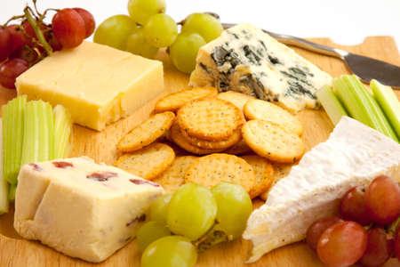 tabla de quesos: Close up de una variedad de queso y guarniciones en un cheeseboard de madera aislada contra un fondo blanco