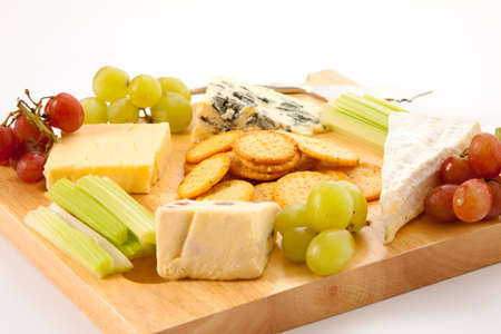 cheeseboard: Close up of a variety of cheese and garnishes on a wooden cheeseboard isolated against a white background