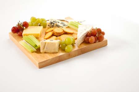 tabla de quesos: Una variedad de quesos con galletas y guarniciones en un cheeseboard de madera aislada contra un fondo blanco