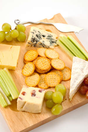 cheeseboard: A variety of cheeses with biscuits and garnishes on a wooden cheeseboard isolated against a white background Stock Photo