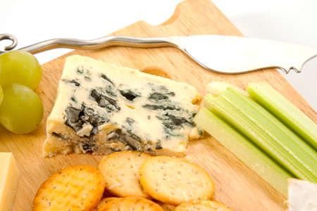 tabla de quesos: Cerca de un trozo de queso Roquefort en un cheeseboard de madera