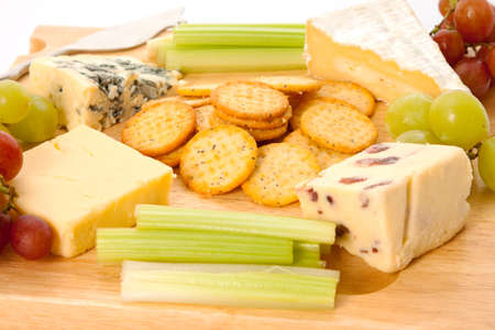 cheeseboard: Close up of a variety of cheese and garnishes on a wooden cheeseboard