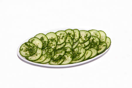 Dish of sliced cucumber isolated against a white background photo