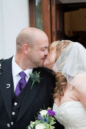 scottish female: A newly married couple kissing outside the church