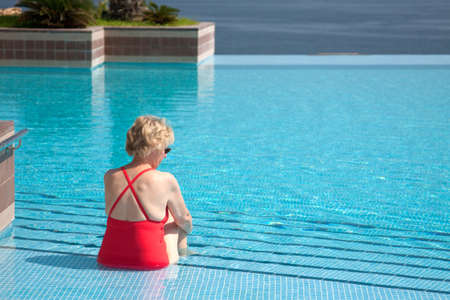 swimming costume: A mature womanin a red swimming costume cooling off in an infinity swimming pool