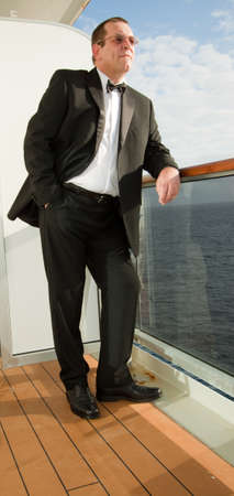 Mature gentleman in a dinner suit gazing out to sea photo