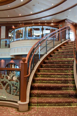 A carpeted staircase leading up to a glass fronted balcony