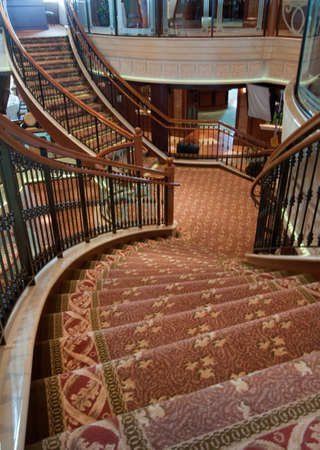 carpet and flooring: A pair of staircases leading left and right from a central landing