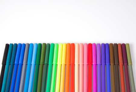 Multicoloured felt tip pens in a row on a white background photo