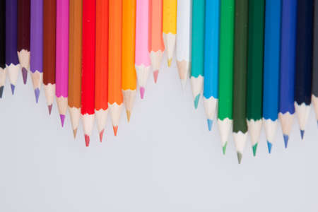 An assortment of coloured pencils isolated against a grey background photo