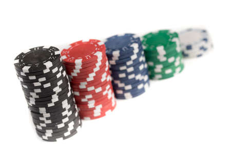 losing money: Stacks of different coloured gaming chips isolated against a white background Stock Photo