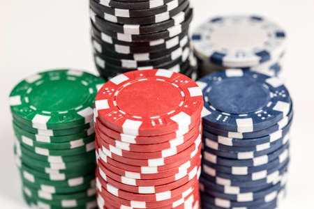 losing money: Close up shot of five piles of different coloured gaming chips isolated against a white background Stock Photo