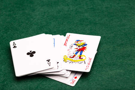 money packs: Deck of cards face-up on a green baize with the Joker poking out of the middle Stock Photo