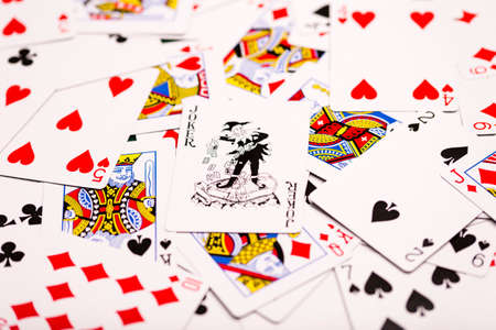 money packs: A pack of playing-cards spread out across the table with a black Joker central