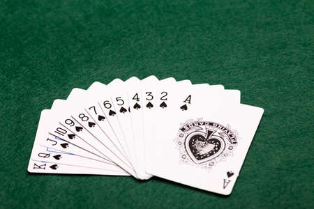 money packs: A full suit of thirteen Spades playing-cards laid out in a fan shape on a green baize background