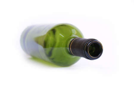 Green wine bottle in soft focus laying down on white background.