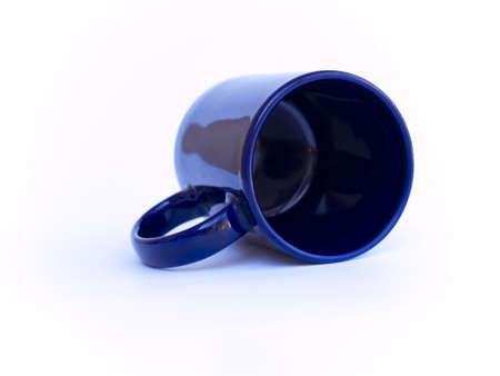 Tasse de caf� bleu sous flou fixant sur fond blanc.