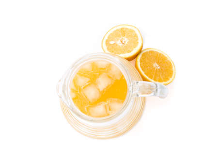 Freshly squeezed orange juice with ice cubes insice a glass jug thats accompanied by two freshly cut orange halves.