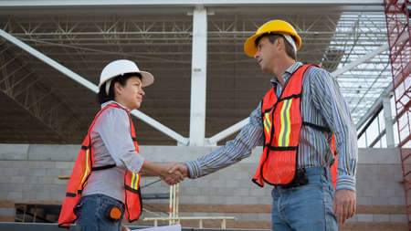 Male and Female Workers Shake Hands Stock Photo